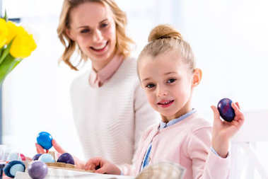 Child showing Easter egg by smiling mother