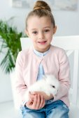 White rabbit sitting on knees of child girl