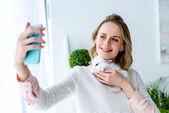 Fotografie Blonde Frau mit weißen Kaninchen und nehmen selfie