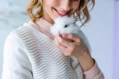 Blonde woman cuddling white bunny
