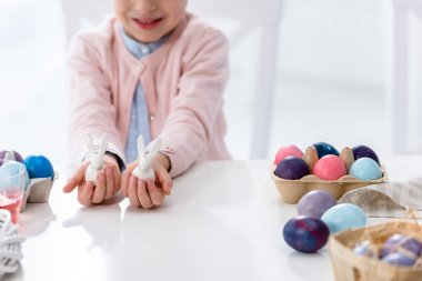 Close-up view of child on Easter holding bunny statuettes by painted eggs