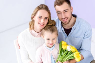 Adorable child and parents holding bouquet of tulips on 8 march