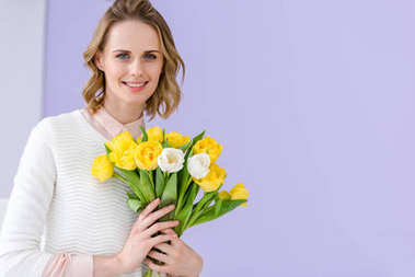 Smiling blonde woman holding bouquet of tulips for 8 march