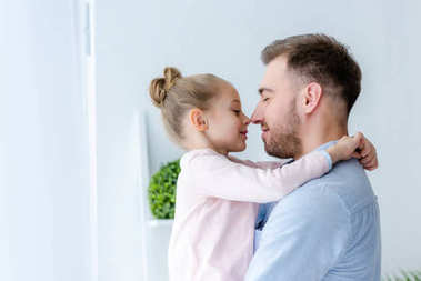 Father and child girl embracing and touching noses