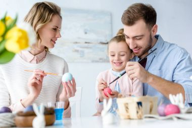 Smiling family with daughter coloring chicken Easter eggs
