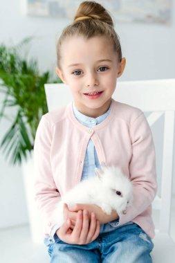 White rabbit sitting on knees of child girl