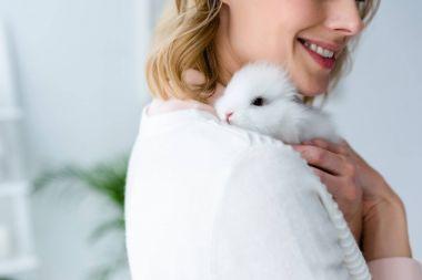 Blonde woman hugging white rabbit