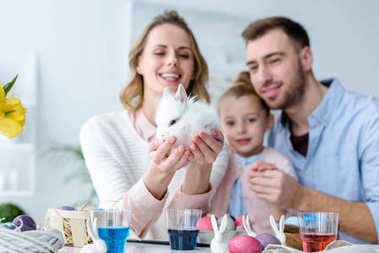 Mother with family holding cute bunny by table with Easter eggs