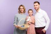 Fényképek Szülők és a lánya gazdaság kosár húsvét tojás elszigetelt Ibolya