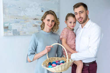 Family celebrating Easter with painted eggs in basket
