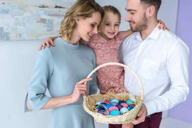 Smiling family holding basket with painted Easter eggs