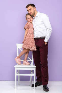 Father embracing little daughter on chair on violet background