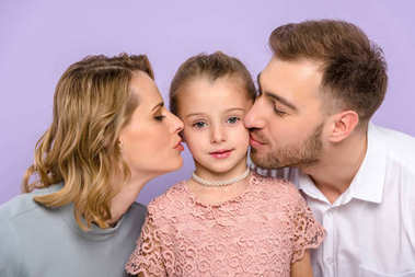 Parents kissing daughter isolated on violet
