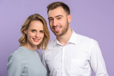 Young smiling couple isolated on violet
