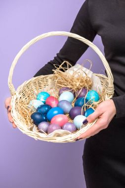Woman holding Easter eggs in basket isolated on violet