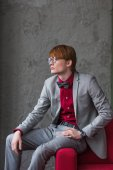 Profil a szemüvegek ruha ül a kanapén szélén öltözött férfi modell