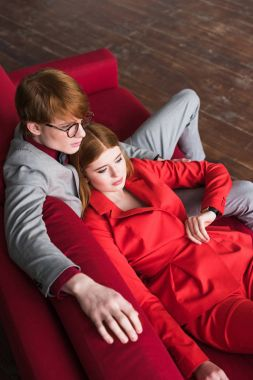 High angle view of stylish male in eyeglasses with lying girlfriend