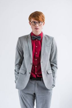 Young male fashion model in eyeglasses with hands in pockets isolated on grey