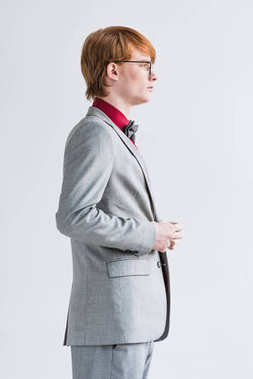 Profile of male fashion model in eyeglasses dressed in suit isolated on grey