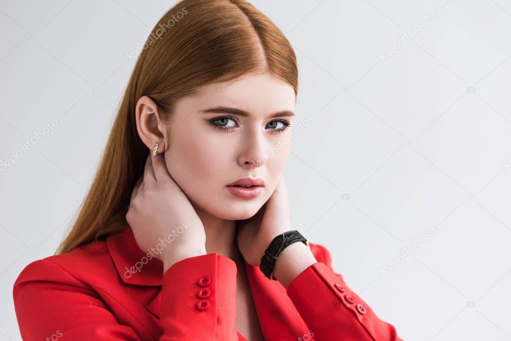 Portrait of female fashion model with wristwatch and earrings isolated on grey