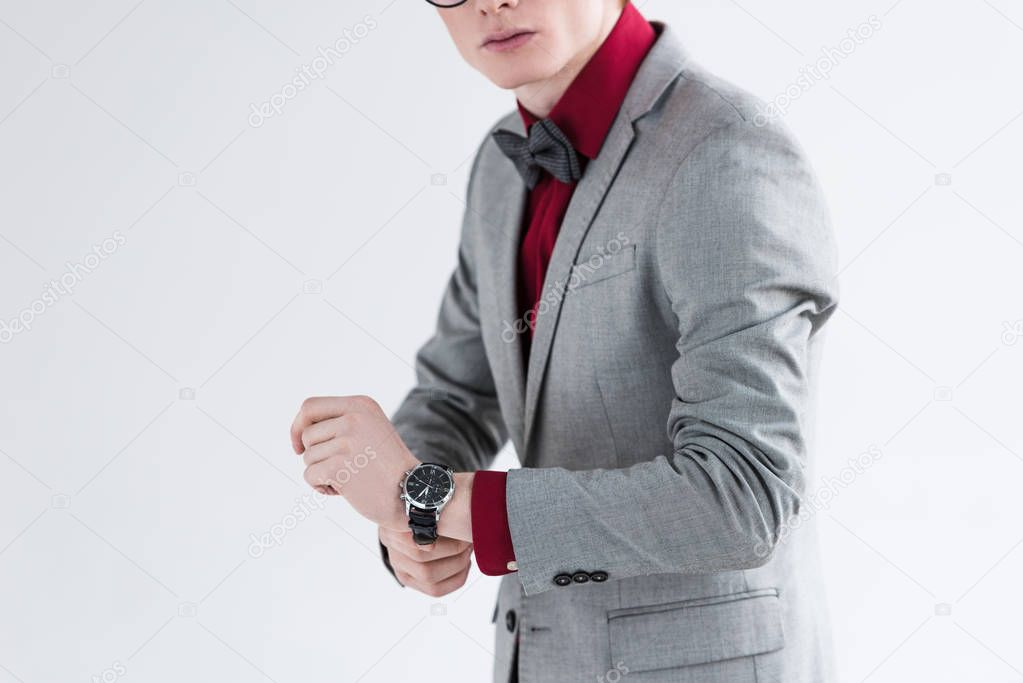 Cropped view of male fashion model in suit adjusting wristwatch