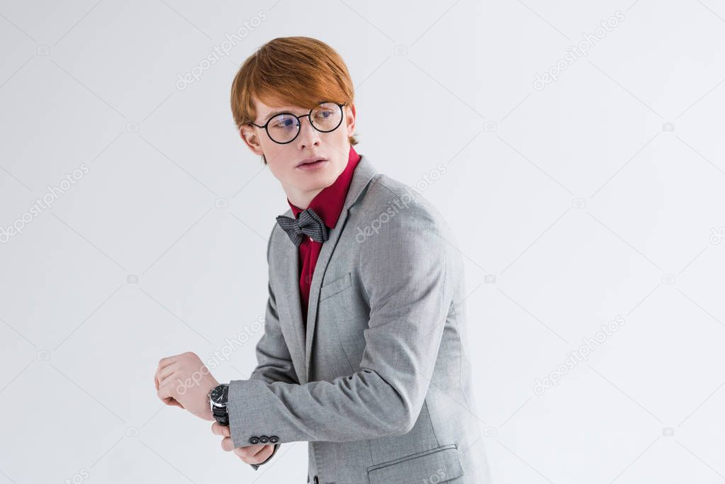 Young male fashion model in eyeglasses adjusting wristwatch isolated on grey