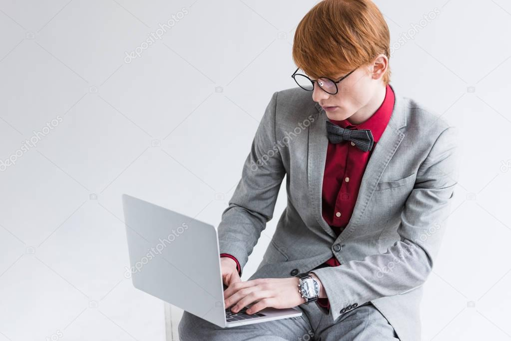 Male fashion model dressed in suit using laptop isolated on grey