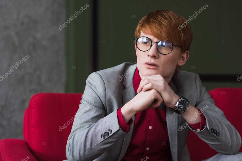 Male fashion model in eyeglasses dressed in suit sitting on red couch