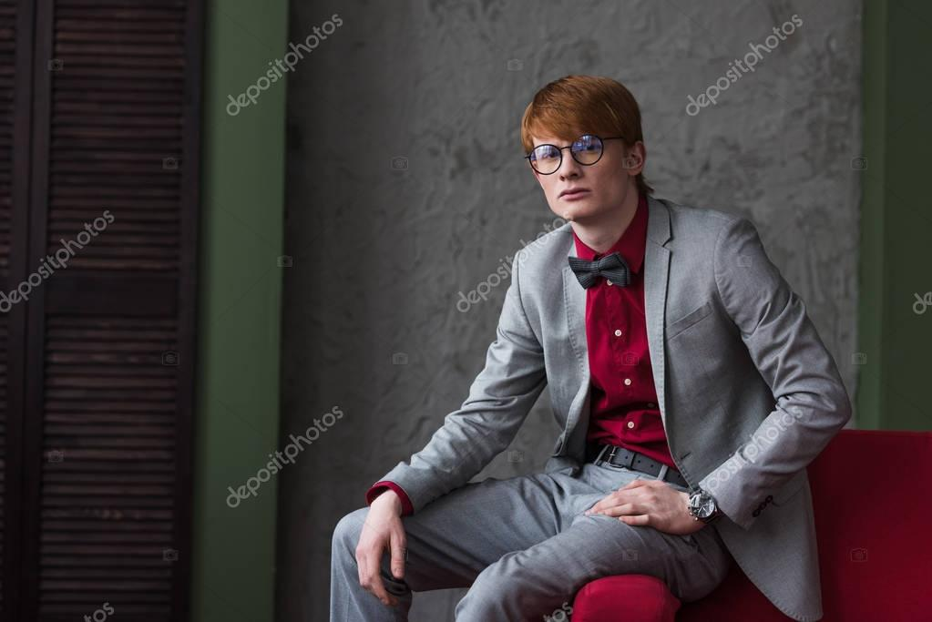 Male fashion model in eyeglasses dressed in grey suit