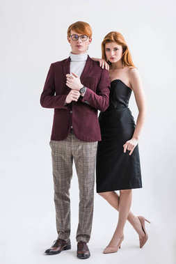 Male fashion model adjusting wristwatch while young female standing beside isolated on grey