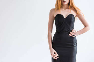 Cropped image of young female fashion model with necklace in black dress isolated on grey
