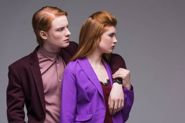 Side view of young fashion models couple isolated on grey
