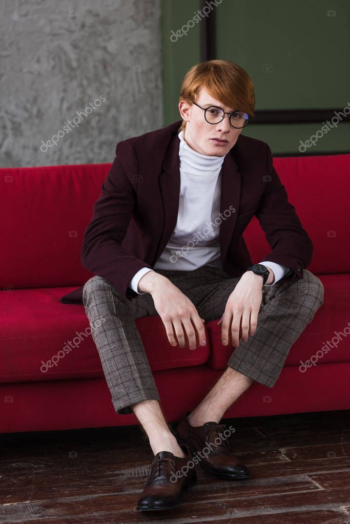 Male model in eyeglasses dressed in jacket sitting on couch