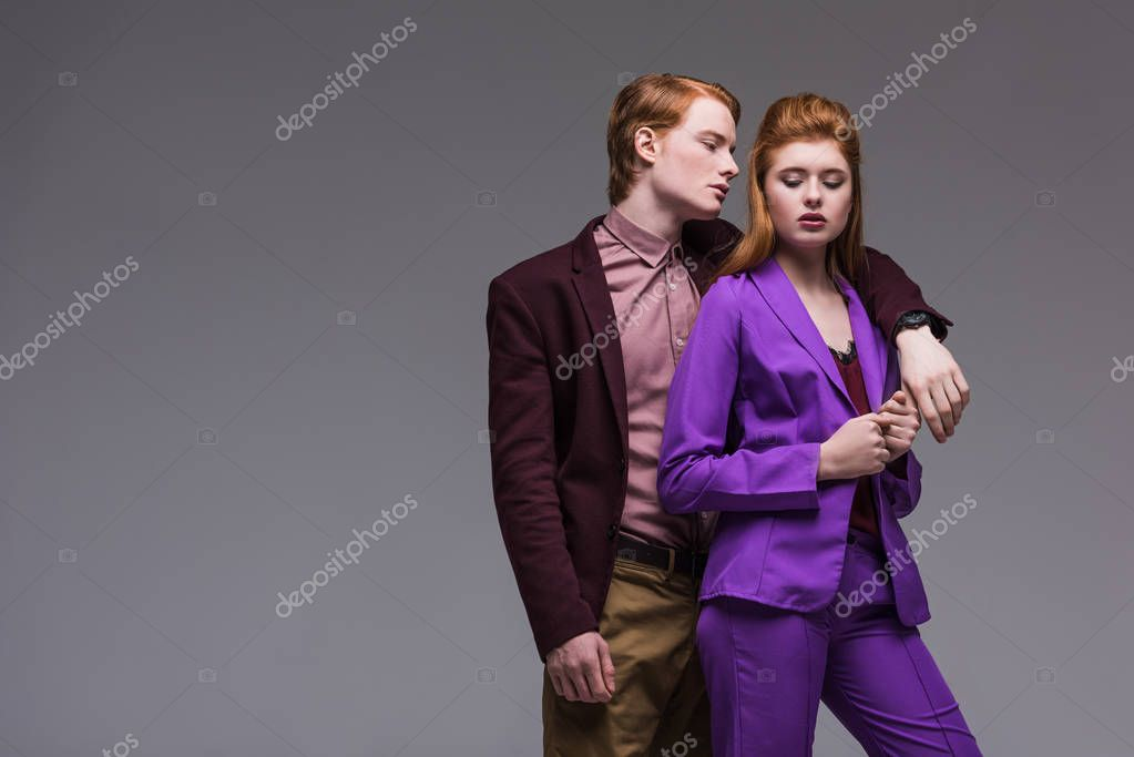 Male fashion model in jacket hugging girlfriend isolated on grey