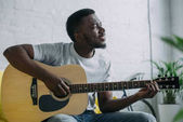 Fotografie smiling young african american man playing acoustic guitar and looking away