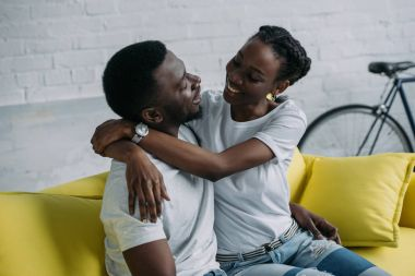 happy young african american couple hugging while sitting on sofa at home