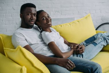 happy young african american couple sitting on sofa and smiling at camera