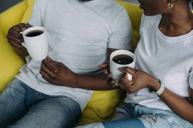 Cropped shot of young african american couple holding cups of coffee at home stock vector