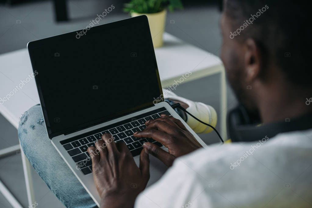 cropped shot of african american man using laptop with blank screen