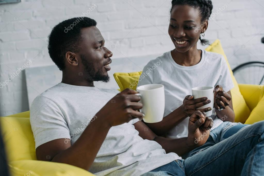 young african american couple drinking coffee and smiling each other at home