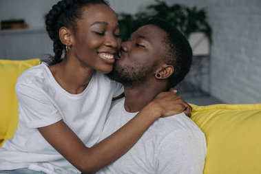 beautiful happy young african american couple hugging and kissing at home