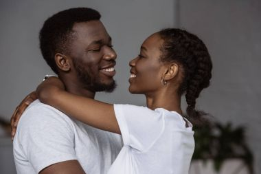 happy young african american couple hugging and smiling each other at home