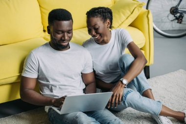 happy young african american couple in white t-shirts using laptop together at home