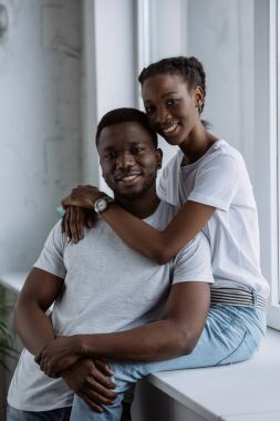 beautiful young african american couple in white t-shirts smiling at camera at home