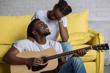 handsome smiling young man playing guitar and looking at beautiful girlfriend at home