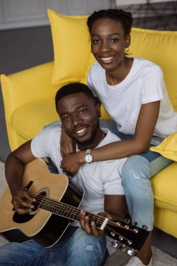 happy young african american couple with acoustic guitar smiling at camera