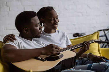 happy young african american couple sitting together on sofa and man playing acoustic guitar