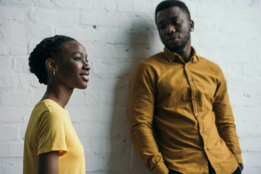 beautiful young african american couple posing in yellow shirts