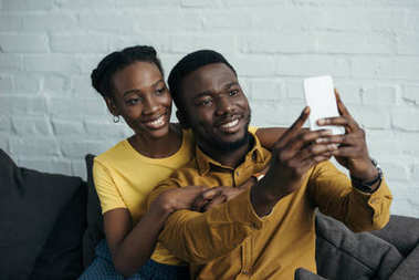 beautiful happy young african american couple taking selfie with smartphone at home