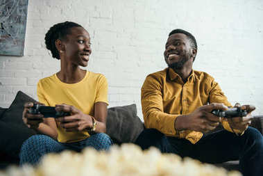 happy young african american couple playing with joysticks and looking at each other